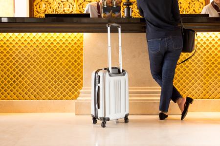 Turysta kobieta z walizką sprawdzić w hotelu recepcji Zdjęcie Seryjne