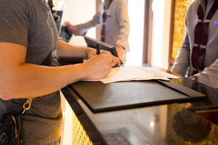 Male guest check in at hotle signing a form at reception counter