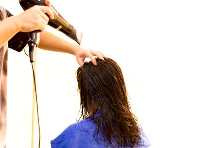 Man hairdresser using blower to dry customer hair in salon