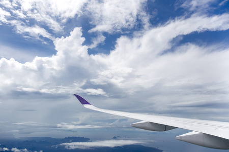 Plane wing flying over white clouds and ocean