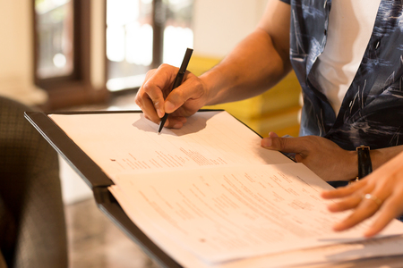 Mans hand signing agreement from for hotel reservation