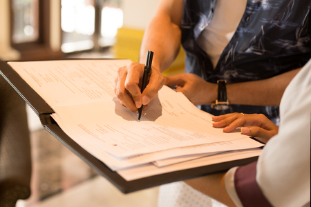 Man hand signing agreement from for hotel reservation Stock Photo