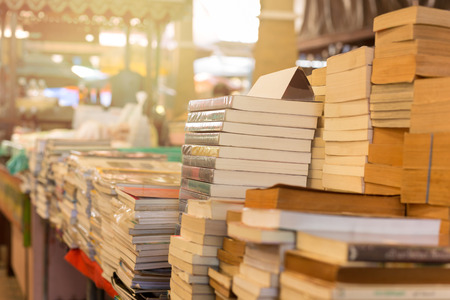 Piles of old books on a table in a market Standard-Bild
