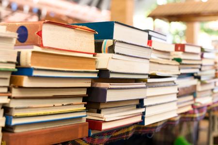 Stapels van oude boeken op een lijst op onduidelijk beeldachtergrond