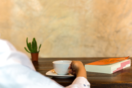 Hand holding coffee cup with book on wooden table and small plant Stock Photo