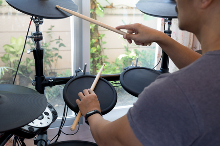 Mans rehearsal playing electronic drums in the house Stock Photo