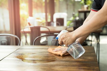 Kelner czyści stół środkiem dezynfekującym w restauracji