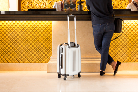 Woman tourist with suitcase chek in at reception hotel