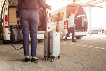 Woman tourist standing with luggage with pick up van at airport Stock Photo