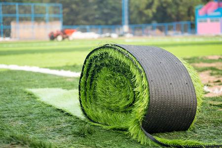 Roll of green artificial grass on new soccer field