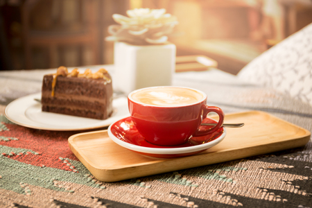 Cup of coffee and piece of macadamia chocolate cake on the table with sunlight