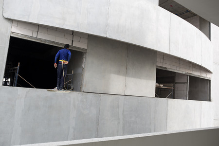 Builder with rope at high building in construction site
