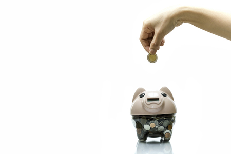 Female hand putting a coin into piggy bank isolated in white background