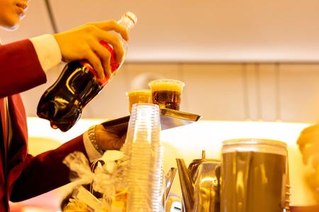 Neergeschoten bij weinig licht. Stewardess die tijdens de vlucht een drankje serveert aan passagiers op stoelen Stockfoto