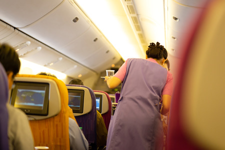 Interior of airplane with passengers on board with flight attendant serving food and beverage