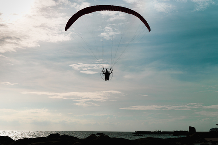 Silhouette paraglider flying on the sea in turquoirs sky background.