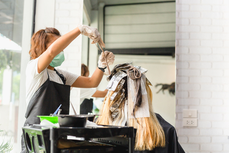 Hairdresser is dying female hair with foil in salon.