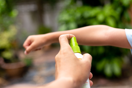Father spraying insect repellents on his son arm in the garden. Banque d'images