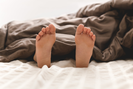 Young boy feet in bed under blanket.
