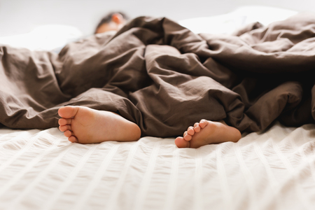 Young boy bare feet in bed under blanket. Stock Photo
