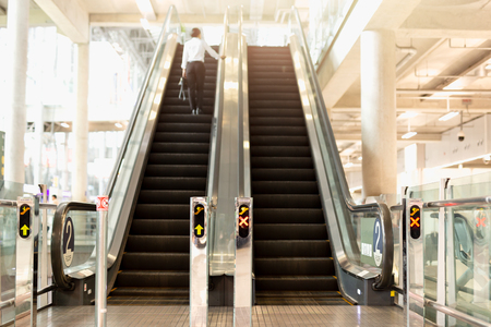 Airport escalator with blurred female backpacker standing in bac 스톡 콘텐츠