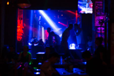 Defocused image - Blurred people with colorful laser lights inside disco club in background. Stock Photo