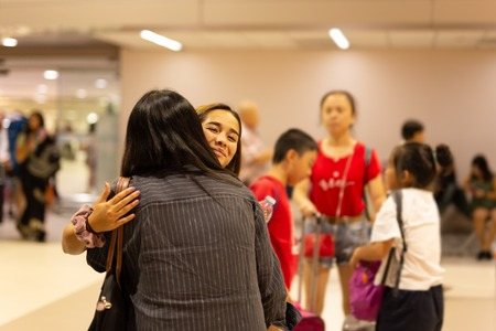 Happy daughter hugging mother on arrival at the airport.