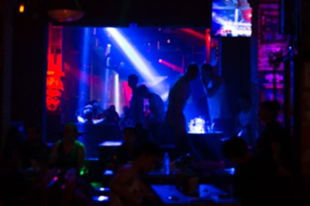 Defocused image - Blurred people with colorful laser lights inside disco club in background