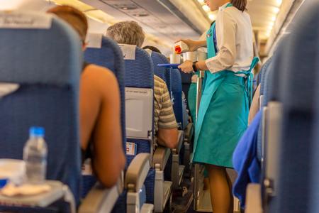 L'assistente di volo serve drink ai passeggeri a bordo.