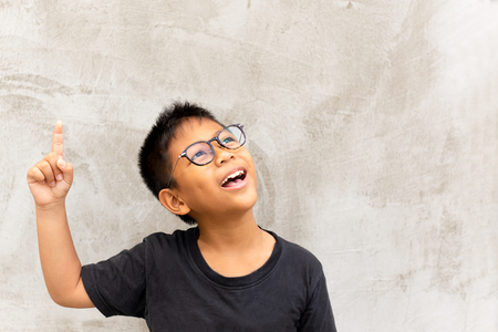 Little asian boy smiling with finger pointing upward. Фото со стока