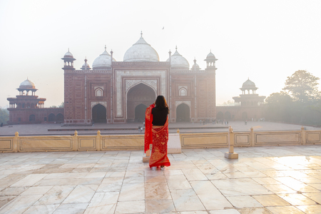 Indian woman in sari taking photo Taj Mahal in the morning.