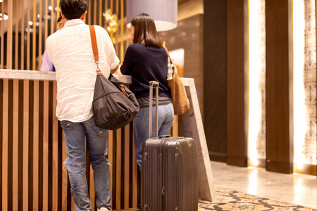 Asian couple with suitcase checking in at hotel reception. Stock Photo