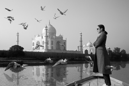 Woman wearing sunglasses standing on a boat with Taj Mahal in background. Stock Photo