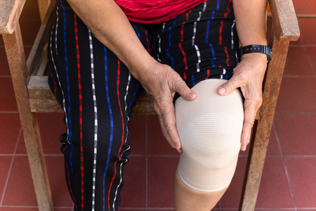 Asian senior woman with bandage compression knee brace support injury.
