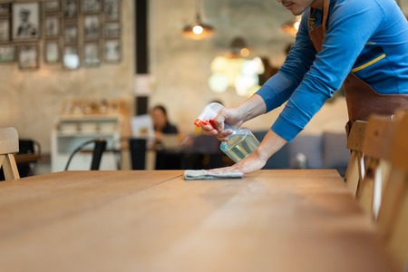 Waiter cleaning the table with spray disinfectant on table in restaurant