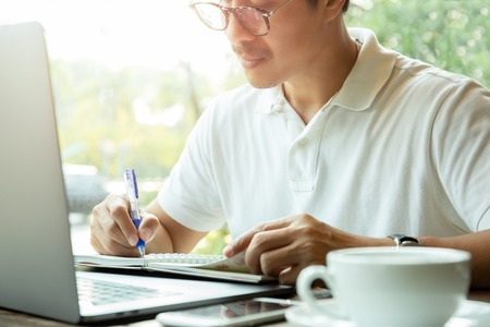 Businessman writing on notepad in front of laptop on wooden desk in coffee shop.