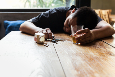 Drunk man holding glass of whiskey and car key sleeping on table with pills. Imagens
