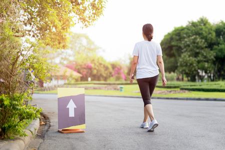 Ejercicio de mujer caminando en el parque con la mano que sostiene el teléfono celular en la mañana.