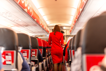 Flight attendant serve food and drinks to passengers on board. Stock Photo