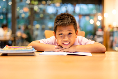 Happy asian boy smiling to camera while doing homework.
