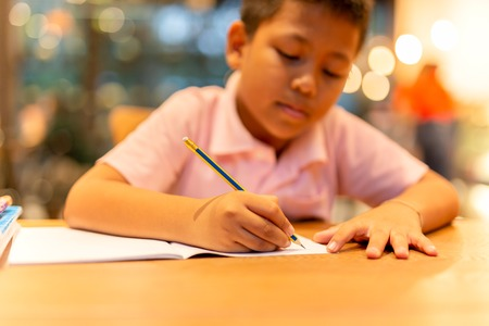 Asian schoolboy hand with pencil doing his homework at home.