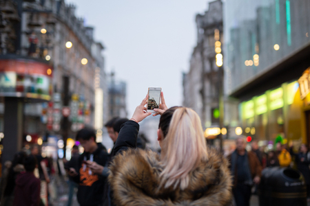 Woman tourist taking pictures of city with her cellphone in blurred