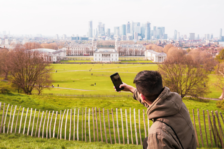 Young man tourist taking pictures in the park with city building