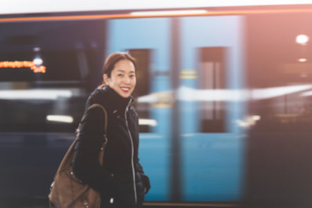 Woman smiling with train moving motion on the station at night blurred concept.