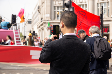 Man taking pictures on smartphone with protest people on street. Imagens