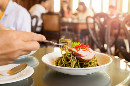 Female having Spaghetti with pesto sauce for lunch in the restaurant.