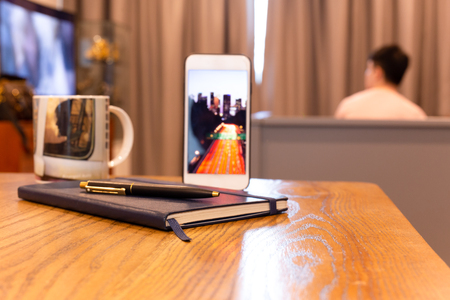 Notebook and pen with cell phone on wooden table in hotel room.