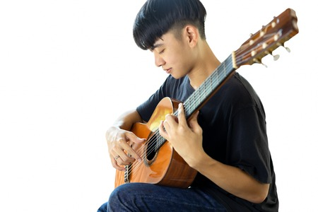 Asian man playing a classic guitar isolated