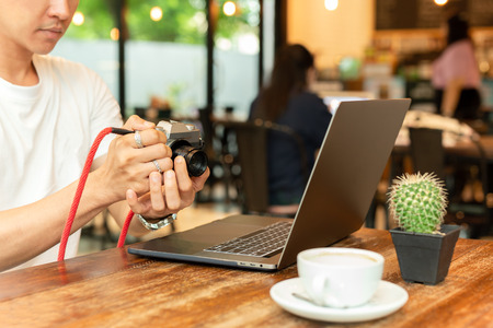 Man holding digital mirrorless camera checking photo with laptop on the table. Stok Fotoğraf