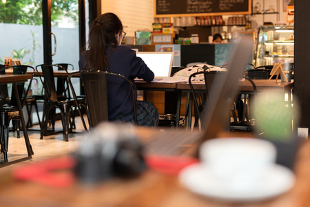 Young woman student working with laptop in cafe.